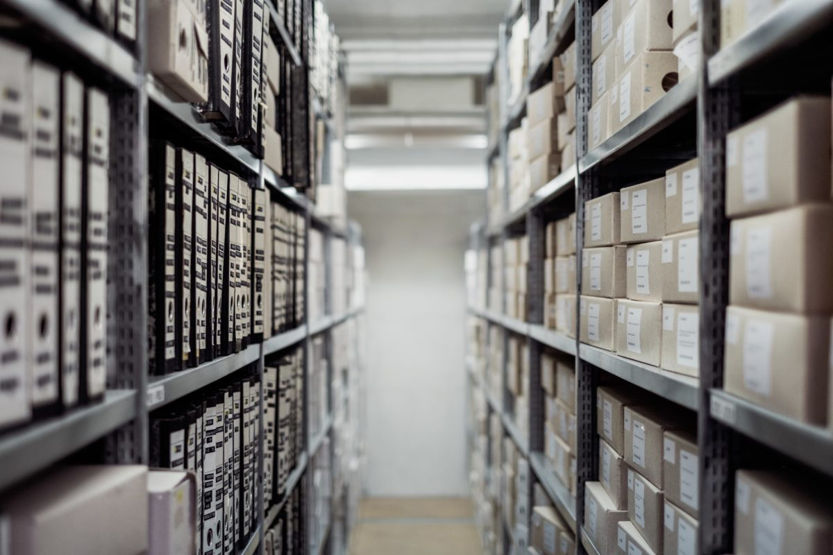 Photo of documents in a lane of shelves in an archive by Samuel Zeller/Unsplash